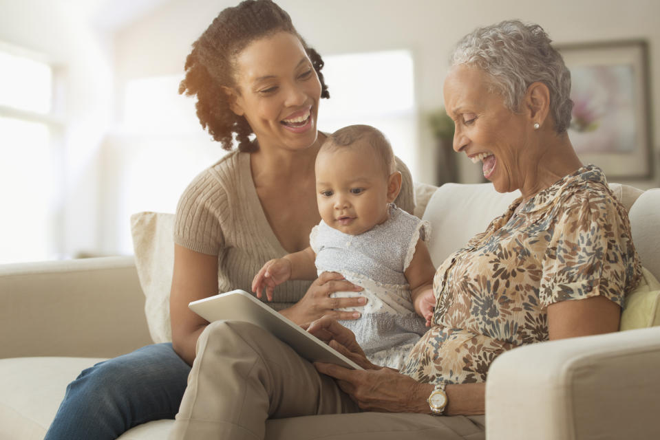 Three generations of women using digital tablet on sofa