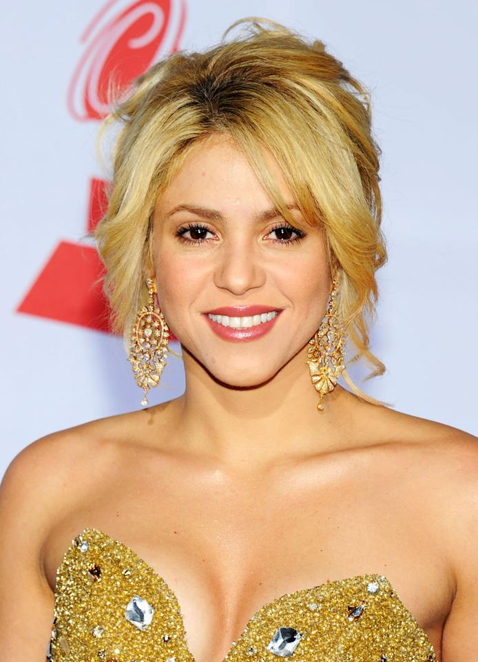 "<p><a class=""sugar-inline-link ga-track"" title=""Latest photos and news for Shakira"" href=""https://www.popsugar.com/Shakira"" target=""_blank"" data-ga-category=""Related"" data-ga-label=""https://www.popsugar.com/Shakira"" data-ga-action=""&lt;-related-&gt; Links"">Shakira</a> surprised everyone at the 12th annual Grammys by arriving with her trademark golden curls in a modern twist with long, face-framing bangs and lots of volume. She kept her makeup simple with a subtle sweep of brown shadow and glossy pink lips. </p>"