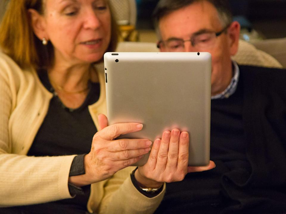 Grandparents having a FaceTime conversation with his granddaughters on an iPad.