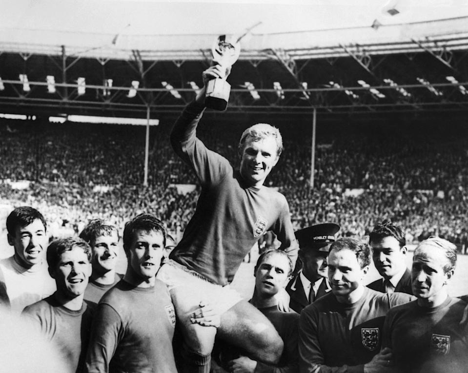 England's national soccer team captain Bobby Moore holds aloft the Jules Rimet trophy as he is carried by his teammates following England's victory over Germany (4-2 in extra time) in the World Cup final 30 July 1966 at Wembley stadium in London.(From L : Gordon Banks, Alan Ball, Roger Hunt, Geoff Hurst - who scored three goals - , Ray Wilson, George Cohen and Bobby Charlton) (Photo by - / CENTRAL PRESS / AFP) (Photo by -/CENTRAL PRESS/AFP via Getty Images)