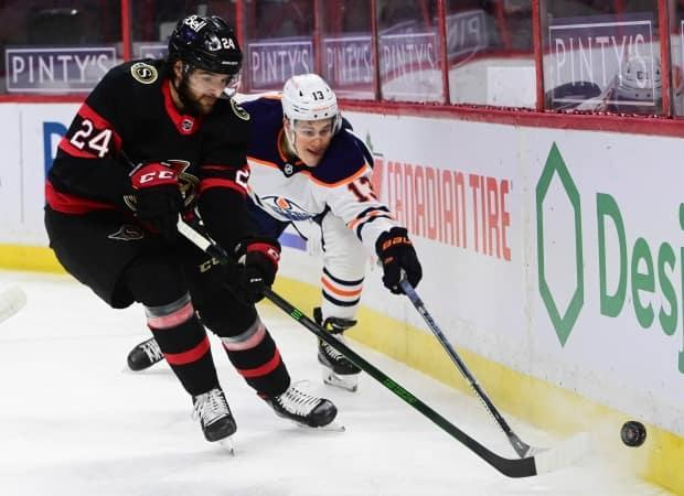 Ottawa Senators defenceman Christian Wolanin (24) and Edmonton Oilers forward Jesse Puljujarvi (13) go for the puck behind the Senators' net during NHL action in Ottawa on Feb. 9. Puljujarvi was placed on the NHL's COVID-19 protocol list later in the week, but has since been cleared to return.