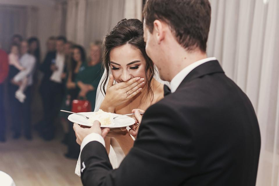 gorgeous bride and stylish groom tasting their stylish wedding cake at wedding reception in restaurant. happy newlywed couple eating piece of cake, funny emotional moment