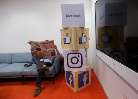 A man reads a newspaper at the reception area of Facebook's new office in Mumbai