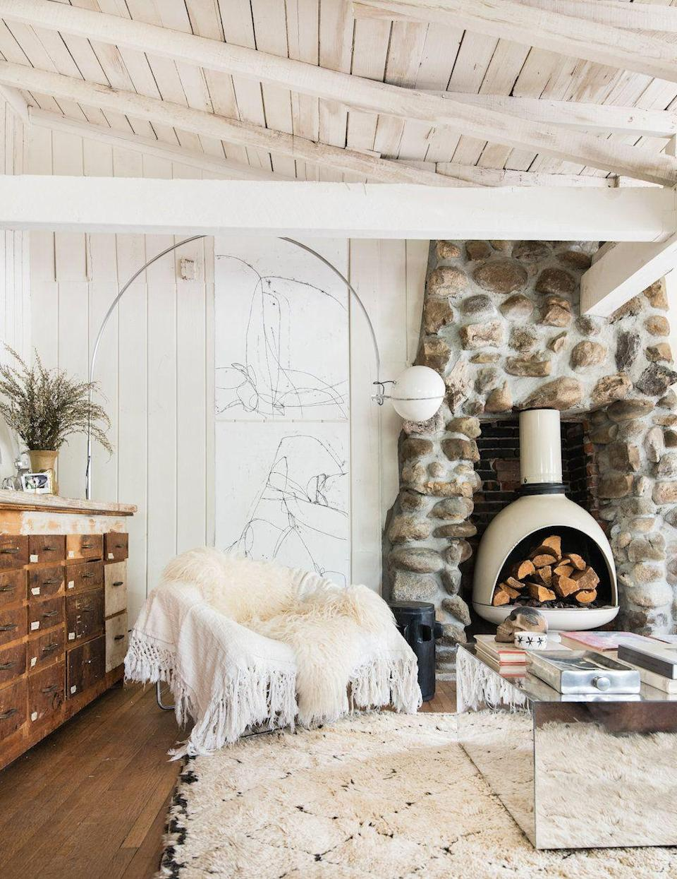 <p>Incorporating mirrored metallics, stone, wood, and plenty of plush throws, this room is covering all the texture bases. We're feeling that stone wall around the wood burning fireplace in particular. The modern updates make it feel on-trend instead of outdated, as does painting everything white. </p>