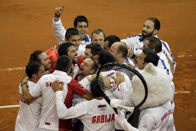 Serbia's national tennis team members celebrate after they had won their Davis Cup semifinals against Canada in Belgrade, Serbia, Sunday, Sept. 15, 2013. (AP Photo/ Marko Drobnjakovic)