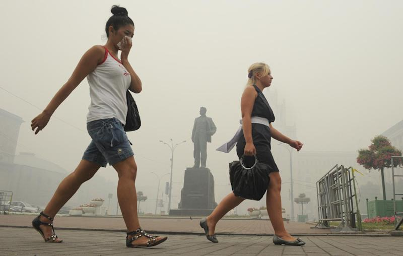Russian women cover their faces to protect themselves from the smog and toxic particles that covered Moscow on August 6, 2010, similar to the smell permeating the city this week (AFP Photo/Alexander Nemenov)