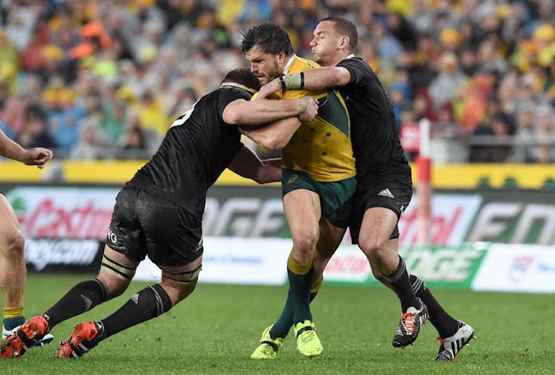 Australian Wallabies centre Adam Ashley-Cooper (C) is tackled by New Zealand All Blacks fly-half Aaron Cruden (R) and no. 8 Kieran Read in their Rugby Championship Test match in Sydney, on August 16, 2014 (AFP Photo/William West)