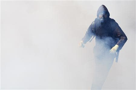 An anti-government protester runs through a cloud of teargas during clashes with police near the Government House in Bangkok December 1, 2013. REUTERS/Kerek Wongsa