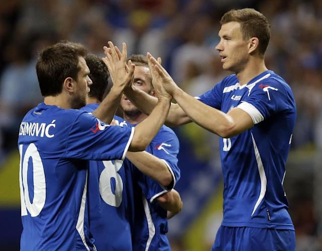 Bosnia-Herzegovina's Edin Dzeko, right, is congratulated by Zvjezdan Misimovic, left, after scoring during the second half in an international friendly soccer match against Ivory Coast on Friday, May 30, 2014, in St. Louis. Dzeko score both goals in the team's 2-1 victory. (AP Photo/Jeff Roberson)
