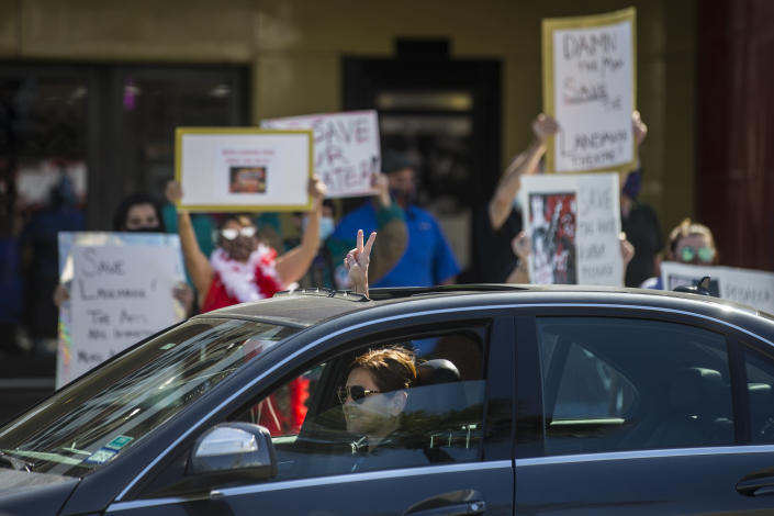 """A driver passing by gives their support to fans and patrons of the Landmark River Oaks Theatre demonstrating against the potential closure of the historic movie theater Sunday, March 7, 2021, in Houston. The historic theater that director Richard Linklater called his """"film school"""" and that for decades was the place to catch hard-to-find independent and foreign films has closed for good. Like many U.S. movie theaters and other businesses, the River Oaks Theatre was a victim of the coronavirus pandemic. ( Brett Coomer/Houston Chronicle via AP)"""