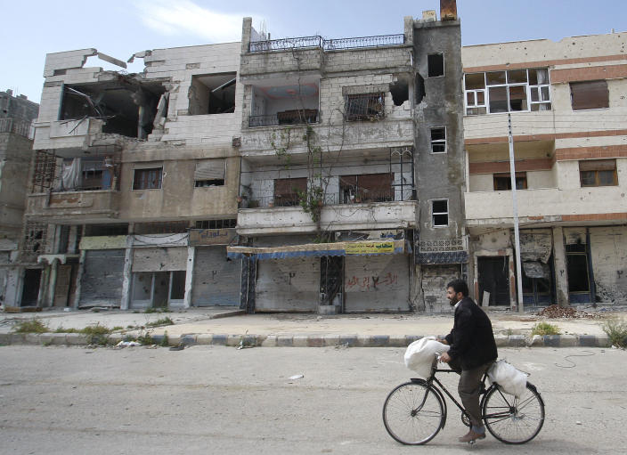 In this picture taken during a UN observer-organized tour, a Syrian man rides his bicycle as he passes destroyed buildings in the Baba Amr neighborhood during the UN observers' visit to Homs city, central Syria, on Thursday, May 3, 2012. Syrian security forces stormed dorms at a northwestern university to break up anti-government protests there, killing at least four students and wounding several others with tear gas and live ammunition, activists and opposition groups said Thursday. (AP Photo/Muzaffar Salman)