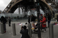 People take picture in front of the Eiffel tower closed after the French government banned all gatherings of over 100 people to limit the spread of the virus COVID-19, in Paris, Saturday, March 14, 2020. For most people, the new coronavirus causes only mild or moderate symptoms. For some it can cause more severe illness, especially in older adults and people with existing health problems. (AP Photo/Christophe Ena)