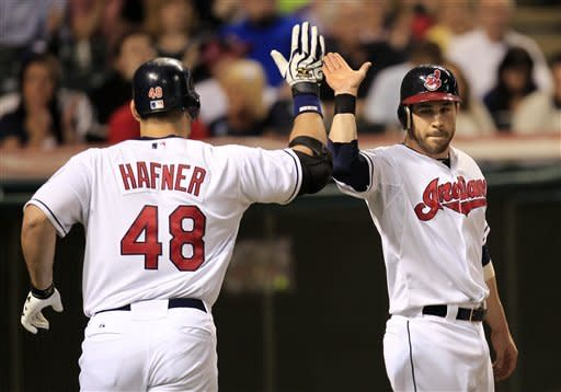 Cleveland Indians' Jason Kipnis, right, congratulates Travis Hafner after Hafner hit a sacrifice fly and Kipnis scored during the sixth inning of a baseball game against the Texas Rangers, Friday, May 4, 2012, in Cleveland. (AP Photo/Tony Dejak)
