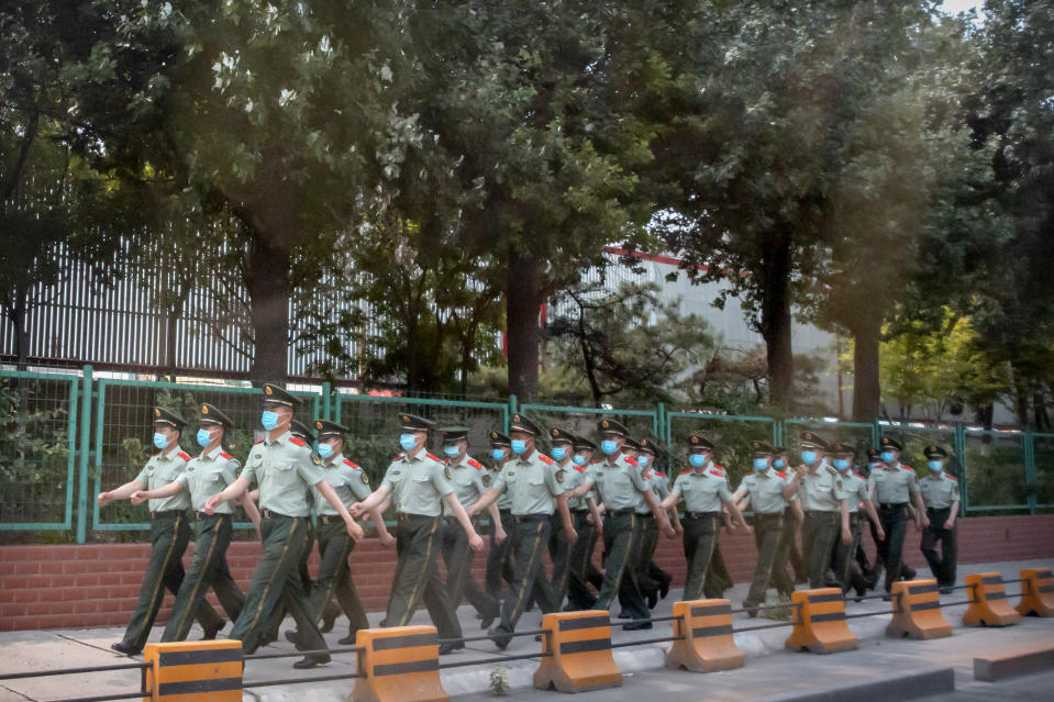 Chinese paramilitary police march in formation outside the Xinfadi wholesale food market district in Beijing, Saturday, June 13, 2020. Beijing closed the city's largest wholesale food market Saturday after the discovery of seven cases of the new coronavirus in the previous two days. (AP Photo/Mark Schiefelbein)