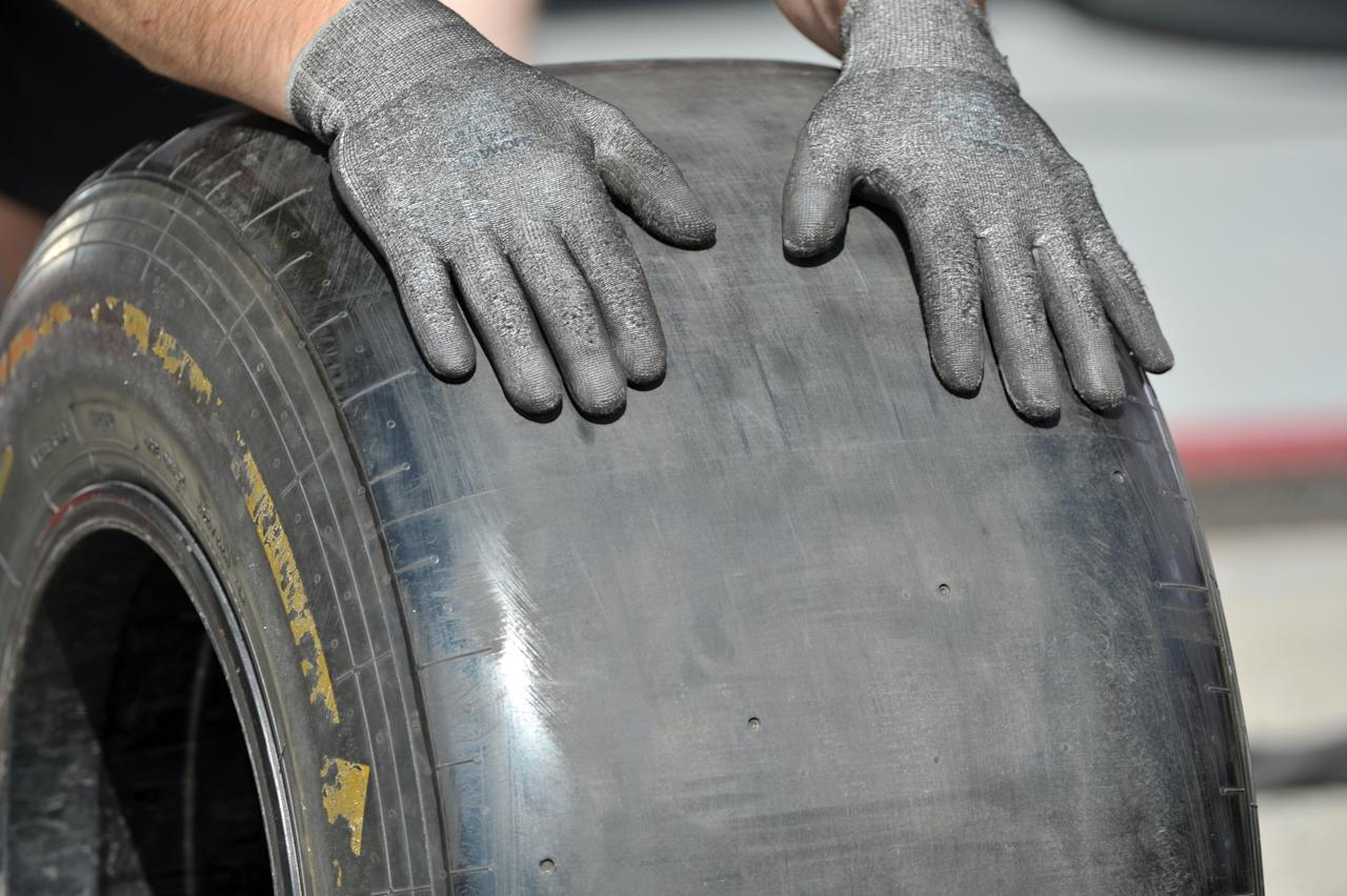 TOPSHOTS A mechanic of McLaren Formula One team holds a tyre at Interlagos motorsport circuit in Sao Paulo on November 22, 2012 ahead of the Brazilian Grand Prix this weekend.  TOPSHOTS/AFP PHOTO/YASUYOSHI CHIBAYASUYOSHI CHIBA/AFP/Getty Images