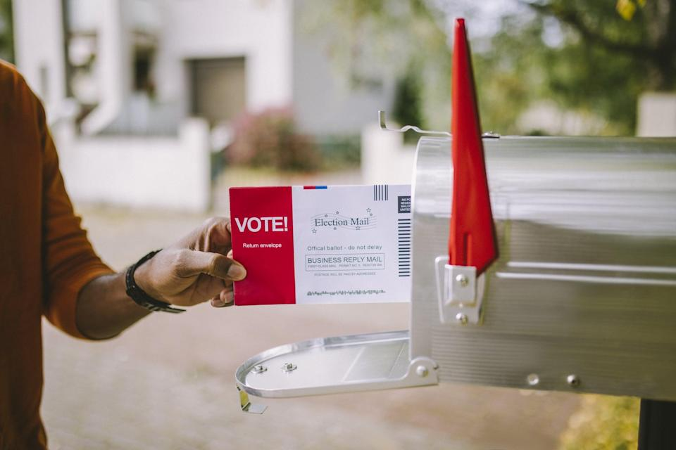 Close up of hand putting voting ballot to mailbox.