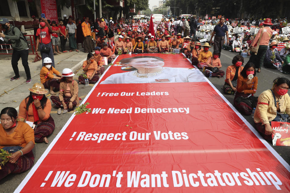 Protesters sit next to a giant banner with images of ousted leader Aung San Suu Kyi during an anti-coup protest in Mandalay, Myanmar, Sunday, Feb. 21, 2021. Police in Myanmar shot dead a few anti-coup protesters and injured several others on Saturday, as security forces increased pressure on popular revolt against the military takeover. (AP Photo)