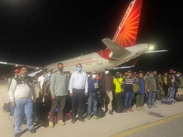 Indian nationals stand behind an Air India plane at Tajikistan's Dushanbe airport.