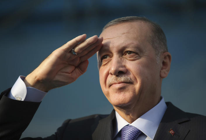 Turkish President Recep Tayyip Erdogan gives a military salute toward his supporters in Kayseri, Turkey, Saturday, Oct. 19, 2019. Turkish Red Crescent says it has delivered humanitarian aid for 2000 people in Syrian town of Ras Al-Ayn and says it also provided aid to Tal Abyad and will continue to do so in areas cleared from Syrian Kurdish fighters.(Presidential Press Service via AP, Pool )
