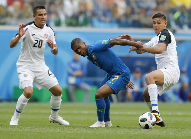 Brazil's Douglas Costa, centre, battles for the ball with Costa Rica's Oscar Duarte, right, as Costa Rica's David Guzman watches during the group E match between Brazil and Costa Rica at the 2018 soccer World Cup in the St. Petersburg Stadium in St. Petersburg, Russia, Friday, June 22, 2018. (AP Photo/Alastair Grant)