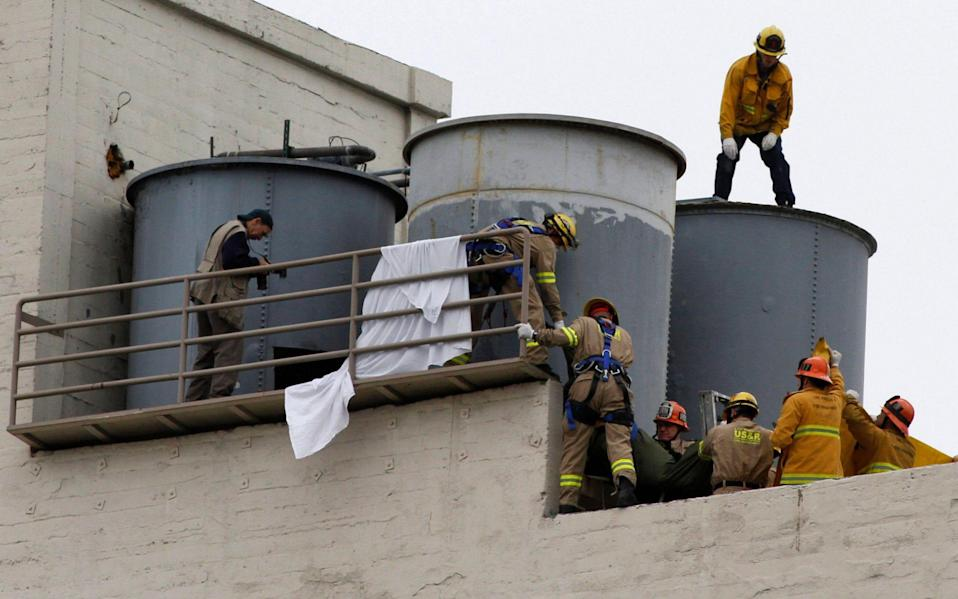 Firefighters work to remove a body found inside a water tank on the rooftop of Hotel Cecil - Alamy