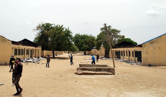 Police officers walking past the Chibok school where more than 200 schoolgirls were abducted by Boko Haram Islamists, April 21, 2014 (AFP Photo/)