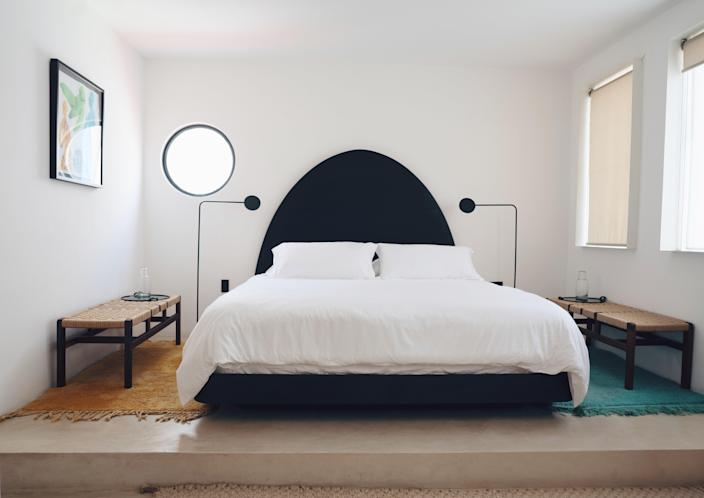 A guest room includes a custom bed designed by Miggi Hood and Ingemar Hagen-Keith, and fabricated by local artisans.