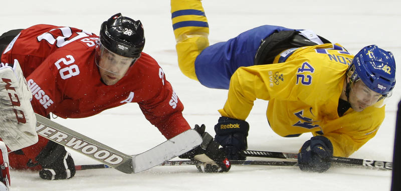 Switzerland forward Martin Pluss (28) and Sweden forward Jimmie Ericsson fall to the ice in the third period of a men's ice hockey game at the 2014 Winter Olympics, Friday, Feb. 14, 2014, in Sochi, Russia. Sweden won 1-0. (AP Photo/Mark Humphrey)
