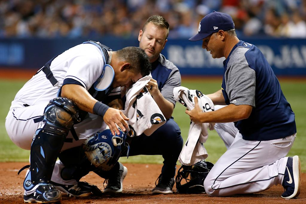 Manger Kevin Cash (R) of the Tampa Bay Rays and a member of medical staff assist catcher Wilson Ramos after Ramos was cut in the head by a broken bat during their game against the Baltimore Orioles, in St. Petersburg, Florida, on July 24, 2017 (AFP Photo/Brian Blanco)
