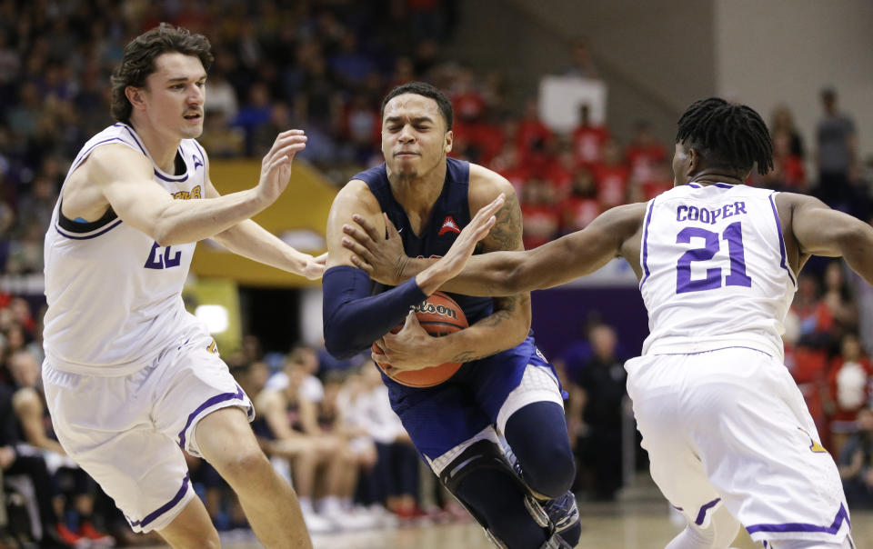 Liberty guard Caleb Homesley drives between Lipscomb defenders Eli Pepper (22) and Kenny Cooper (21) in the first half of the Atlantic Sun NCAA college basketball tournament championship game Sunday, March 10, 2019, in Nashville, Tenn. (AP Photo/Mark Humphrey)