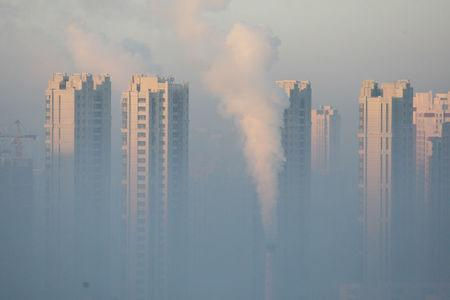 FILE PHOTO - A chimney is seen in front of residential buildings during a polluted day in Harbin