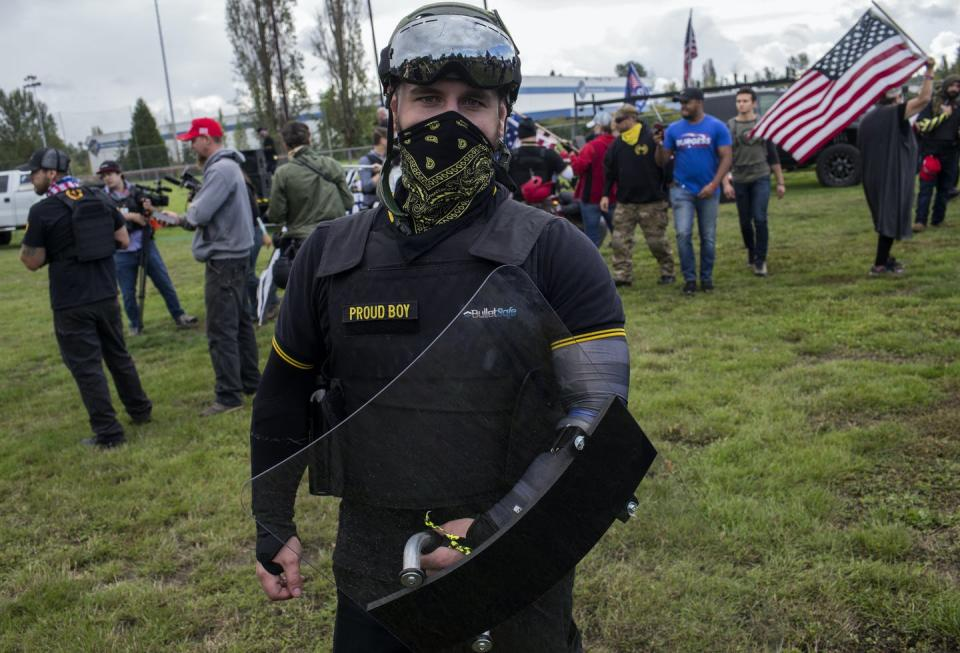 Picture of a man wearing military gear and the name 'Proud Boys' with an American flag in background