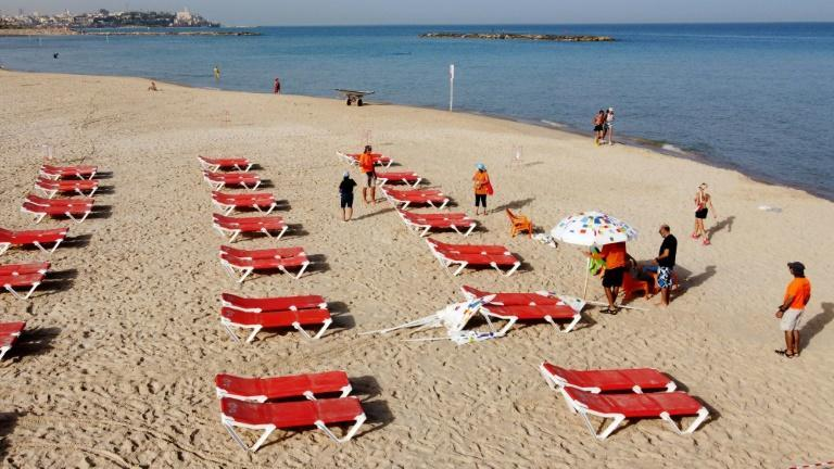 Beach attendants were busy arranging deckchairs and parasols in the sand, spacing them out to comply with new distancing regulations (AFP Photo/JACK GUEZ)