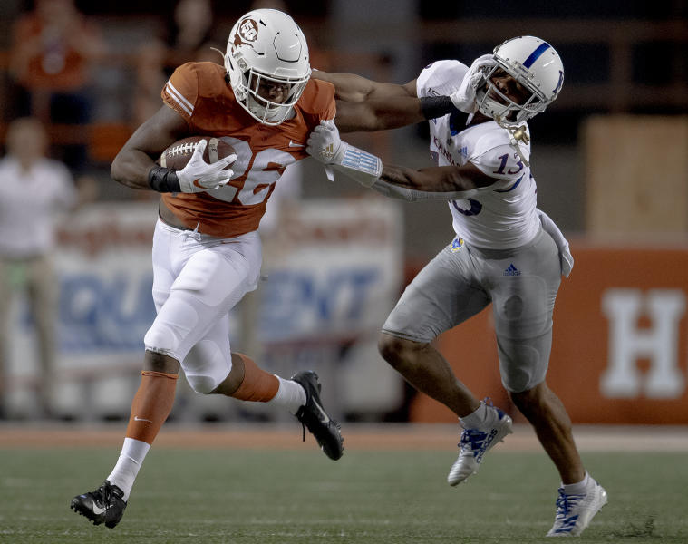 Texas running back Keaontay Ingram (26) stiff-arms Kansas cornerback Hasan Defense (13) during an NCAA college football game Saturday, Oct. 19, 2019, in Austin, Texas. (Nick Wagner/Austin American-Statesman via AP)