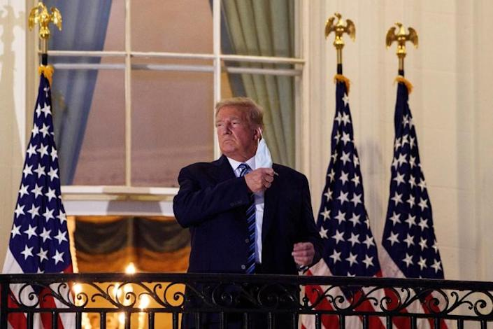 President Donald Trump remove his mask on the balcony of the White House