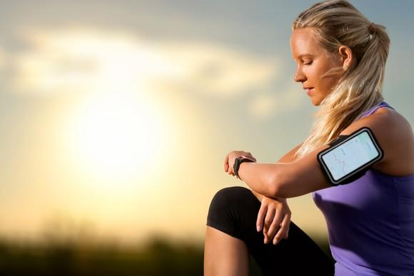 A blonde-haired woman in a purple shirt and black leggings takes a break from a run to check her wearable fitness device at sunset