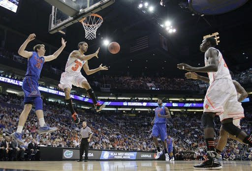 Louisville's Peyton Siva (3) passes to teammate Gorgui Dieng, right, as Florida's Erik Murphy, left, watches during the first half of an NCAA tournament West Regional final college basketball game, Saturday, March 24, 2012, in Phoenix. (AP Photo/Matt York)