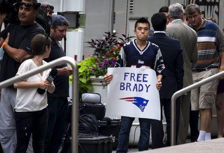 A supporter of New England Patriots quarterback Tom Brady holds a sign as he stands with a large crowd of media outside the National Football League (NFL) headquarters offices in Manhattan, New York City, June 23, 2015. REUTERS/Mike Segar
