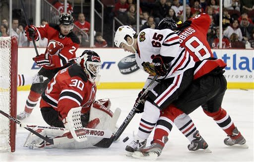 New Jersey Devils goalie Martin Brodeur (30) stops a shot by Chicago Blackhawks' Andrew Shaw (65) as Dainius Zubrus (8), of Lithuania, defends in the first period of an NHL hockey game, Tuesday, March 27, 2012, in Newark, N.J. (AP Photo/Julio Cortez)