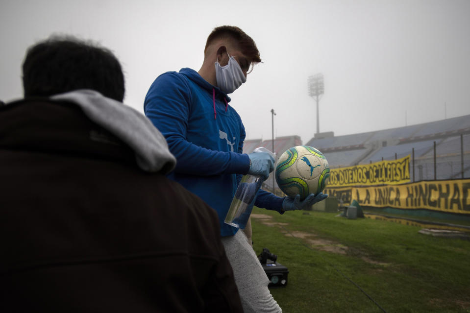 A ball catcher wearing plastic gloves and a face mask amid the coronavirus pandemic, disinfects the ball during a local championship soccer match between Nacional and Penarol in Montevideo, Uruguay, Sunday, Aug. 9, 2020. (AP Photo/Matilde Campodonico)