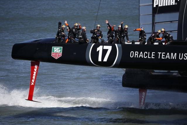 Members of Oracle Team USA wave to spectators after winning Race 17 of the 34th America's Cup yacht sailing race against Emirates Team New Zealand in San Francisco, California September 24, 2013. REUTERS/Stephen Lam (UNITED STATES - Tags: SPORT YACHTING)