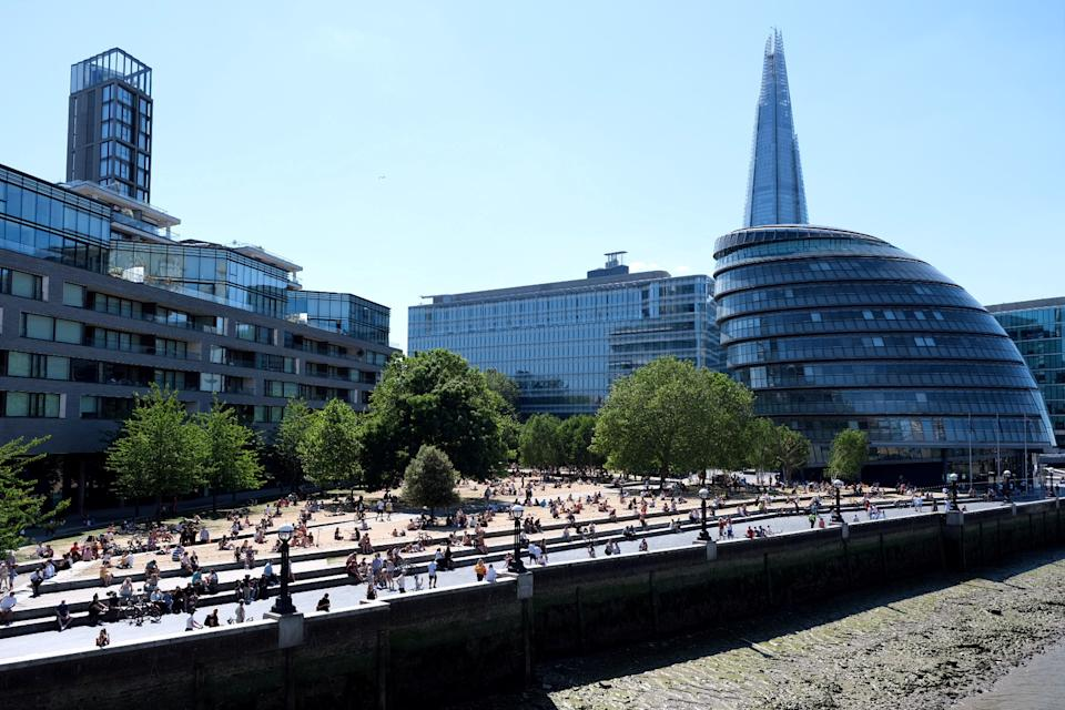 The Shard and the City hall are seen as people enjoy the hot weather on the bank of the River Thames in London, following the outbreak of the coronavirus disease (COVID-19), London, Britain, May 31, 2020. REUTERS/Steven Watt