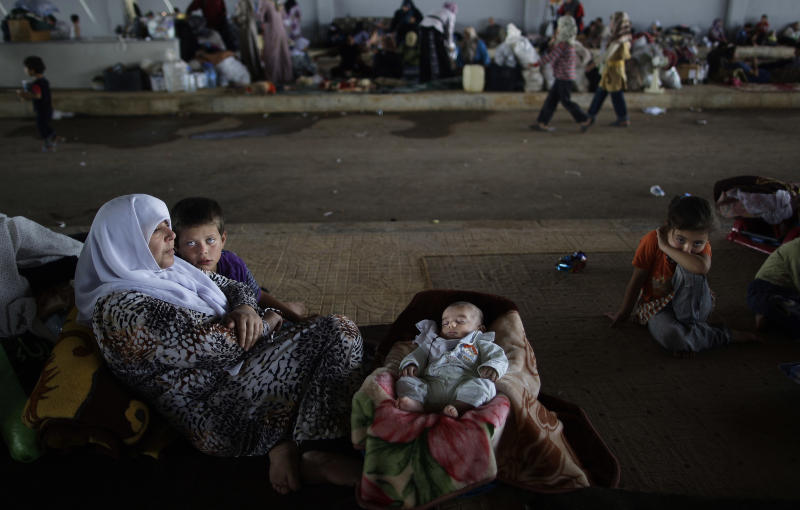 A Syrian family, who fled their home, due to fighting between the Syrian army and the rebels, take refuge at the Bab Al-Salameh border crossing, in hopes of entering one of the refugee camps in Turkey, near the Syrian town of Azaz, Wednesday, Aug. 29, 2012. (AP Photo/Muhammed Muheisen)