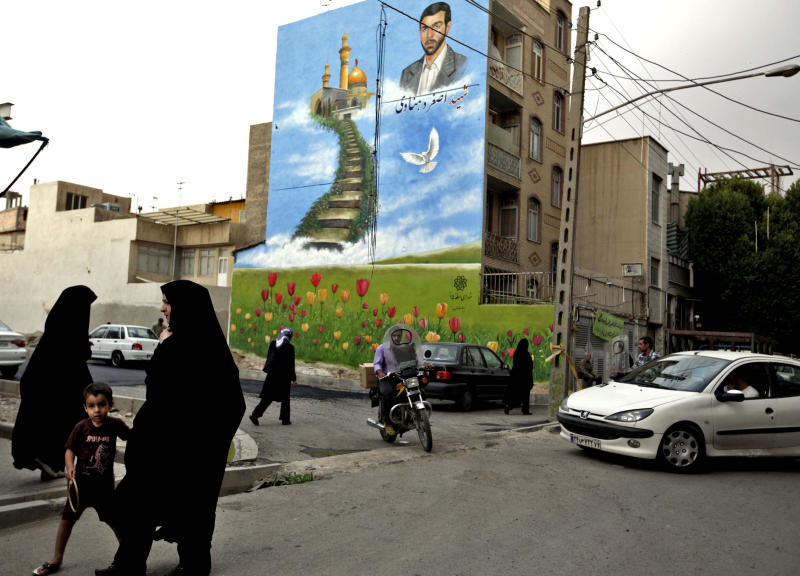 In this Tuesday, May 28, 2013 photo, Iranian pedestrians make their way, under a mural showing Ali Asghar Dehnadi, who was killed during 1980-88 Iran-Iraq war, in downtown Tehran, Iran. On the roughneck streets in south Tehran, paramilitary volunteers look to the most hard-line presidential candidate as the best defender of the Islamic system. On the other end of Tehran's social ladder, a university professor plans to snub next week's election. In between is a mix of splintered views, apathy and indecision based on dozens of AP interviews suggesting a still wide open race. (AP Photo/Vahid Salemi)