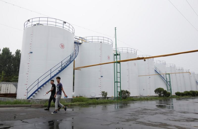 Men walk past oil tanks at the plant of Liangyou Industry and Trade Co., Ltd in Qufu, Shandong province, China July 4, 2018. REUTERS/Jason Lee