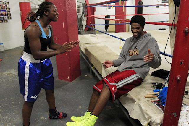 In this Sept. 18, 2012, photo, Olympic gold medal boxer Claressa Shields shares a laugh with training partner Ardreal Holmes at the Berston Field House in Flint, Mich. Aside from her Olympic title and a jab that could knock someone out cold, Shields isn't much different than other high school seniors. (AP Photo/Carlos Osorio)