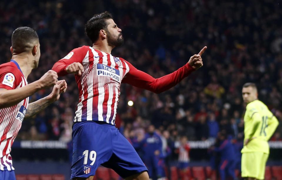 Atletico's Diego Costa, center, celebrates after scoring the opening goal during a Spanish La Liga soccer match between Atletico Madrid and FC Barcelona at the Metropolitano stadium in Madrid, Saturday, Nov. 24, 2018. (AP Photo/Paul White)