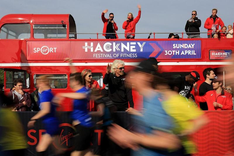 Support: Sir Richard Branson waves off runners after starting the half marathon (PA)