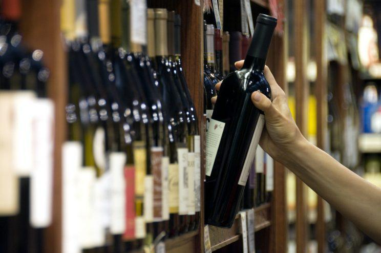 A woman's hand reaches out to select a bottle of red wine from the shelf of a wine shop. (Photo: AFP)