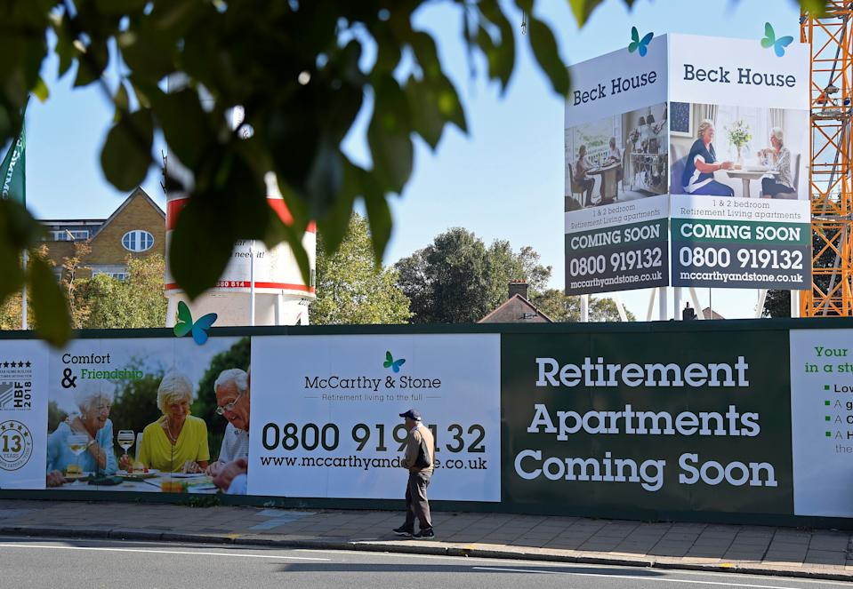 A man walks past hoardings advertising retirement apartments currently being built behind on site by McCarthy & Stone in London, Britain, October 10, 2018. REUTERS/Toby Melville